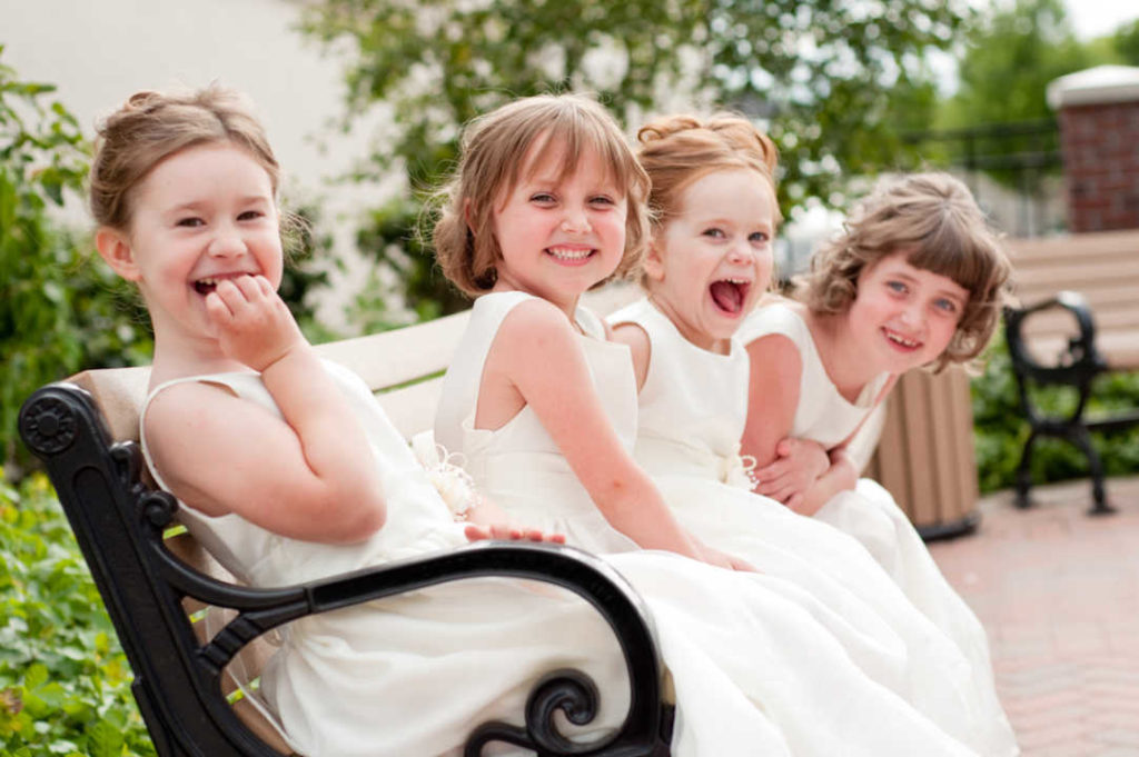 Four Happy Little Flower Girls Laughing Together in Formal Dresses